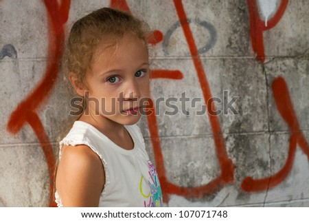 sad little girl on background the wall with graffiti - stock photo