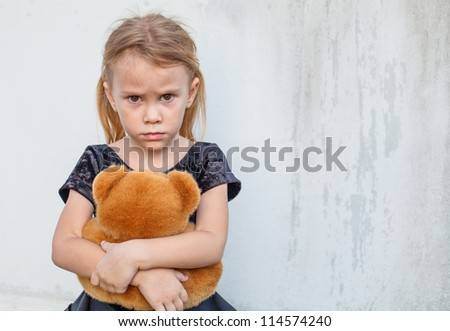 sad little girl on background the wall with toy - stock photo