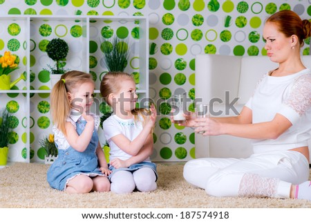 Sad little girl refuses to drink a glass of milk mother angry - stock photo