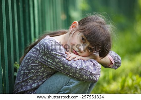 Sad little girl sitting alone on the nature - stock photo