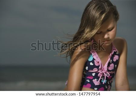 Sad little girl sitting at a beach - stock photo