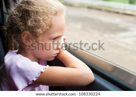 sad little girl sitting in the car near the window - stock photo