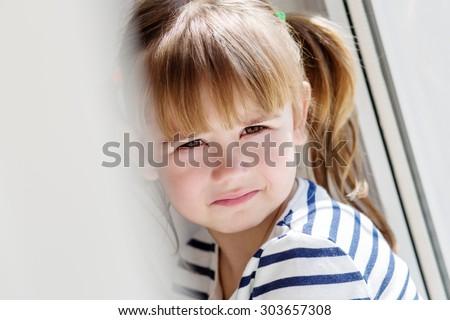 sad little girl sitting near the window - stock photo