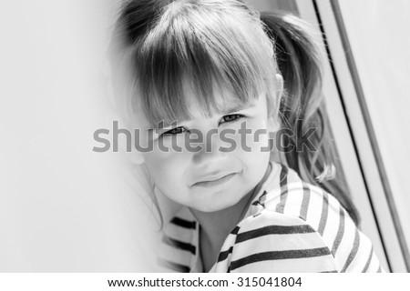 sad little girl sitting near the window  ( black and white ) - stock photo
