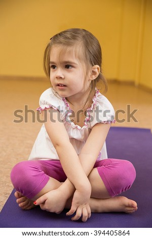 sad little girl sitting on a mat in the gym - stock photo