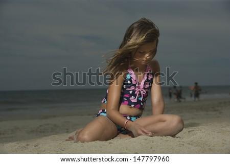 Sad little girl sitting on sand at a beach - stock photo
