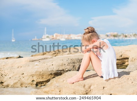 Sad little girl sitting on the beach. Place for text. - stock photo
