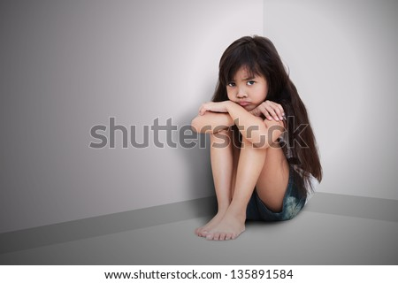 Sad little girl sitting on the floor - stock photo