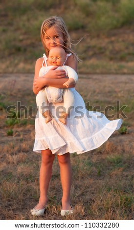 Sad little girl standing alone and holding her baby toy on sunny summer day. - stock photo