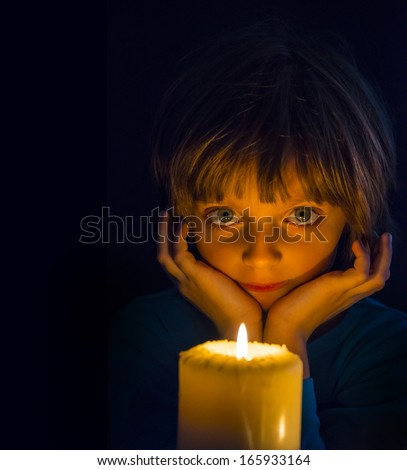 sad little girl with a candle - stock photo