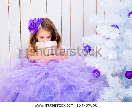sad little girl with a gift in hands near white Christmas tree - stock photo