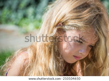 sad little girl with blond hair - stock photo