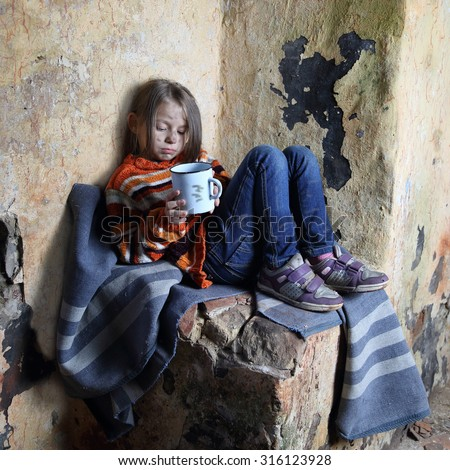 Sad little girl with dirty face sits on old blanket in basement with iron mug in hands - refugee orphan, poverty concept - stock photo