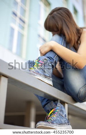 Sad lonely girl meditates sitting on the railing of the city (focus on trendy sneakers) - stock photo