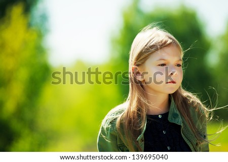 Sad lonely girl staying in the forest and hair blowing in the wind - stock photo