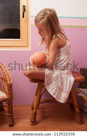 Sad lonely little girl sitting on small table in her room while holding baby toy. - stock photo