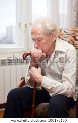 sad lonely old man sitting in an armchair with his cane - stock photo