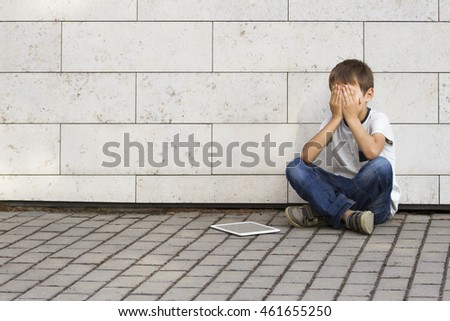 Sad, lonely, unhappy, disappointed child sitting alone on the ground. Boy holding his head, look down. The tablet pc computer near him. Casual clothes. Outdoor