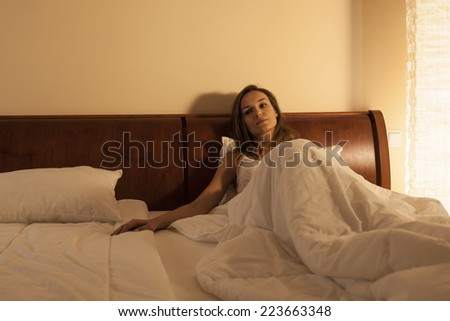 Sad lonely woman lying in bed at night - stock photo