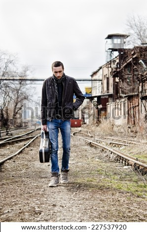 Sad lonely young man with guitar case in hand going by the rails  - stock photo