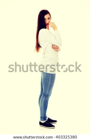 Sad lonely young woman biting her nail - stock photo