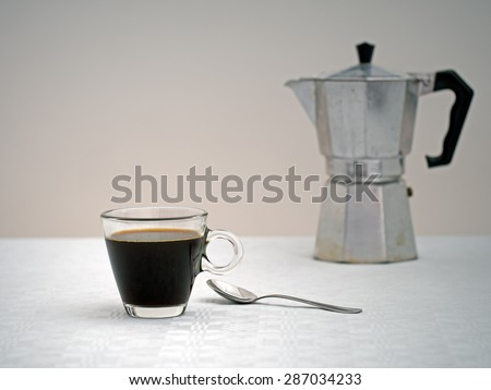 Sad looking coffee and old espresso machine, blurry, in distance.  Focus on cup. Coffee for one, loneliness concept.