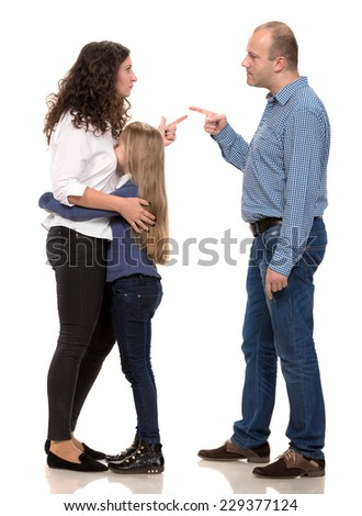 Sad looking girl with her fighting parents on a white background - stock photo
