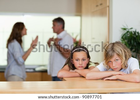 Sad looking siblings with their arguing parents behind them - stock photo