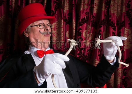 Sad magician holding a broken rope as his trick went wrong