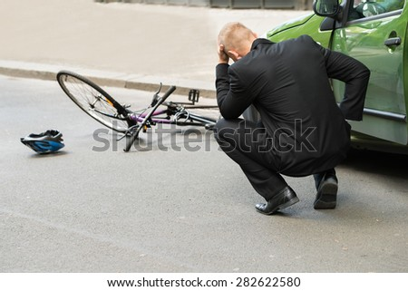 Sad Male Driver After Collision With Bicycle On Road - stock photo