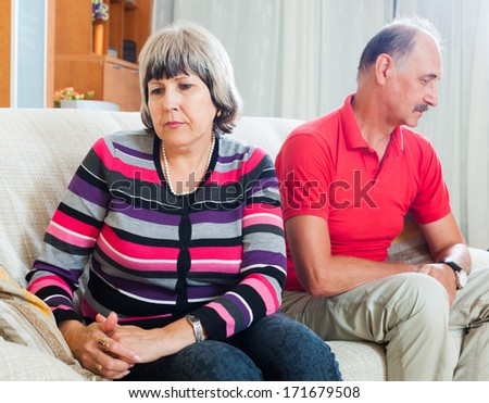 Sad man and woman during quarrel  in living room - stock photo