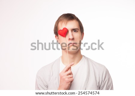 Sad Man covering his eye with a heart. Isolated over white background. - stock photo