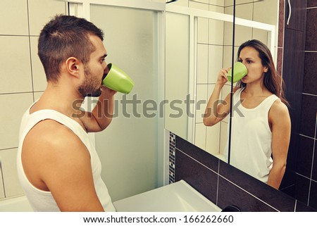 sad man drinking tea and looking at a woman in the mirror - stock photo