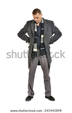 Sad man in coat looking down on a white background - stock photo