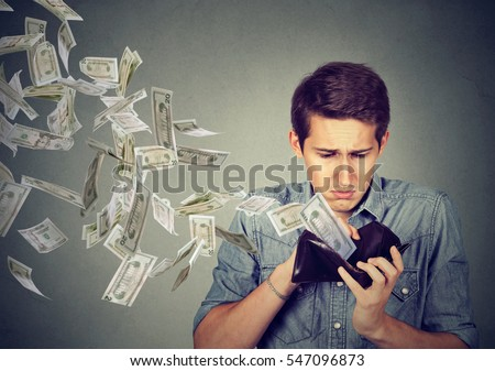 Sad man looking at his wallet with money dollar banknotes flying out away