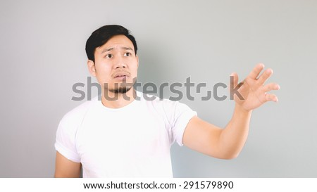 Sad man reaching hand as not to left him behind. An asian man with white t-shirt and grey background. - stock photo
