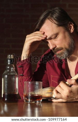 Sad man sits quietly at his home at the table