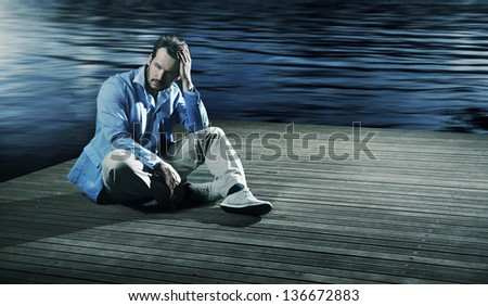 Sad man sitting on a pier