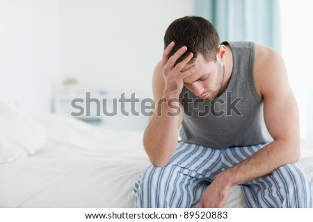 Sad man sitting on his bed with his head on his hand - stock photo