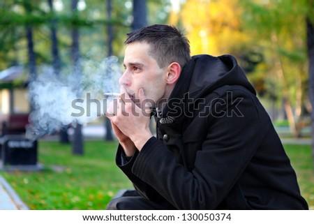 Sad man smoking cigarette in the autumn park - stock photo