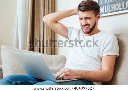Sad man using laptop computer on the sofa at home