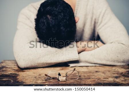 Sad man with broken glasses is in despair - stock photo