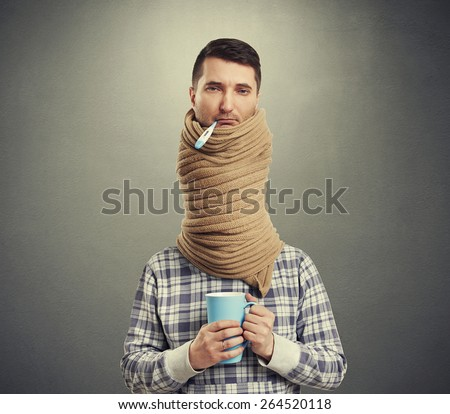 sad man with long neck coiled scarf over dark background - stock photo