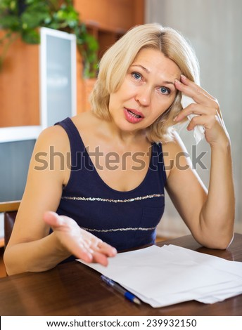 Sad mature blonde woman filling in financial documents at table in home interior