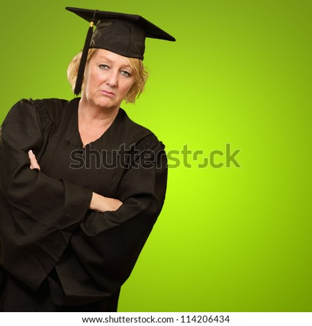 Sad Mature Graduate Woman With Arm Crossed Isolated On Green Background - stock photo