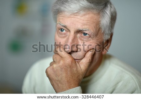 Sad mature man holding head with hand