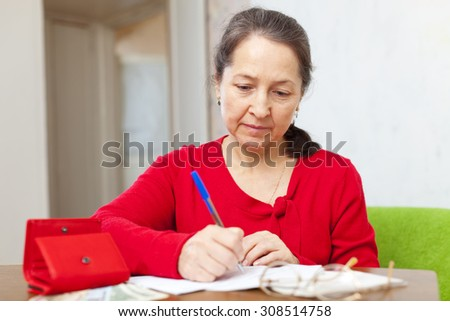 Sad mature woman fills utility bills at her home - stock photo