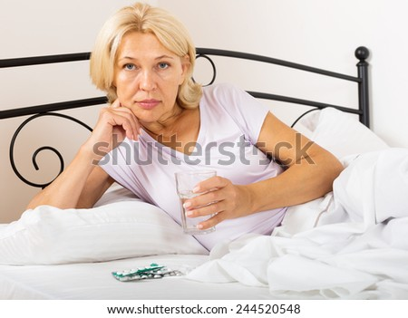 Sad mature woman laying with pills and glass of water - stock photo