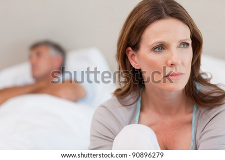 Sad mature woman on bed with her husband in the background - stock photo