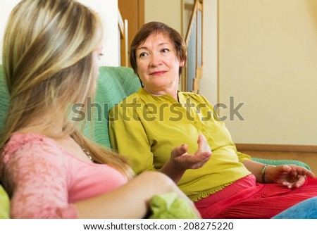 Sad mature woman with adult daughter  sharing bad news at home - stock photo